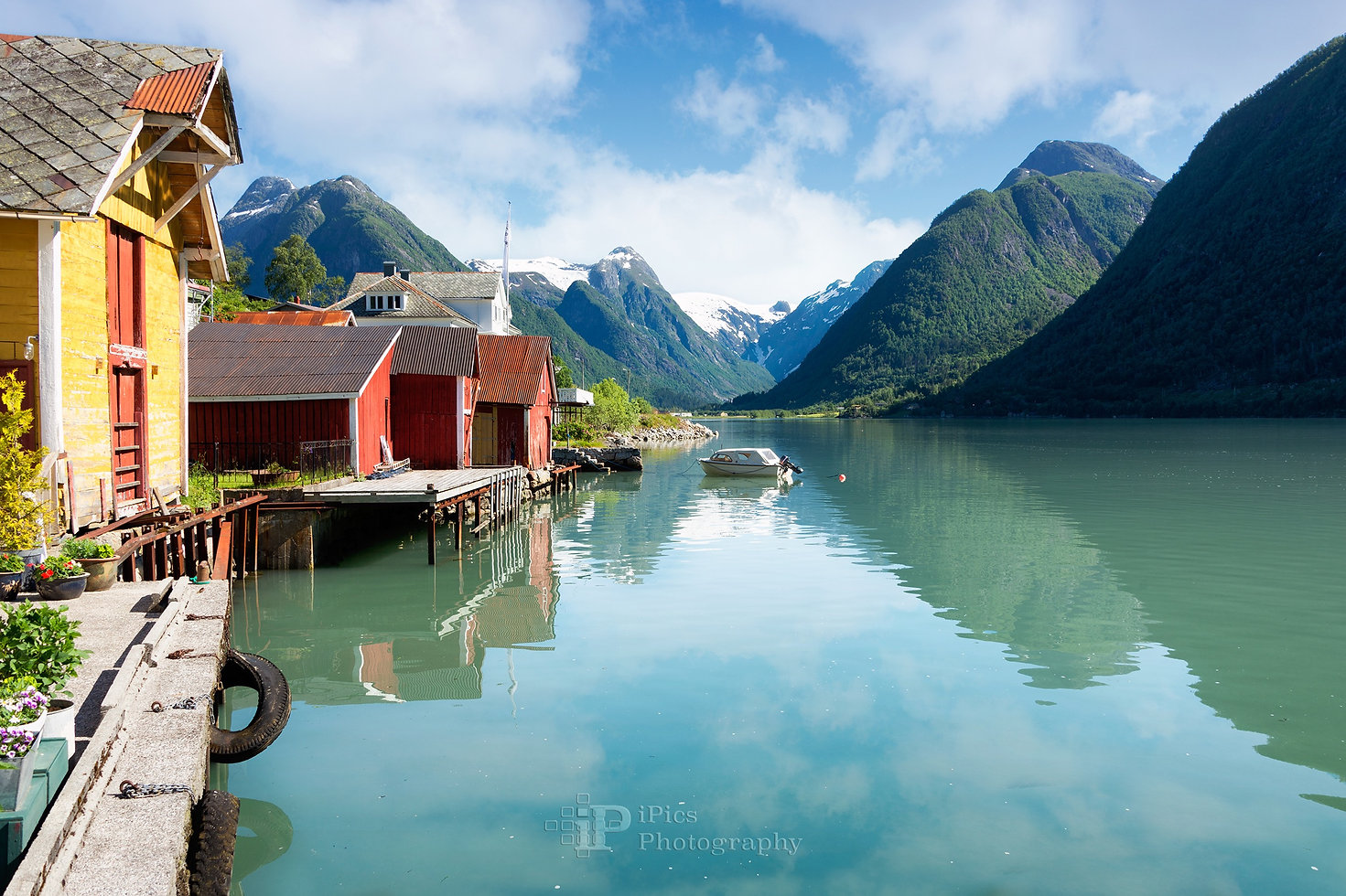 Landscape photograph of the fjord Fjaerlandsfjord and the village of Fjaerland (Mundal) with colorful houses, snow-capped mountains, a boat and clouds in the sky in a landscape in Sogn og Fjordane, Norway.