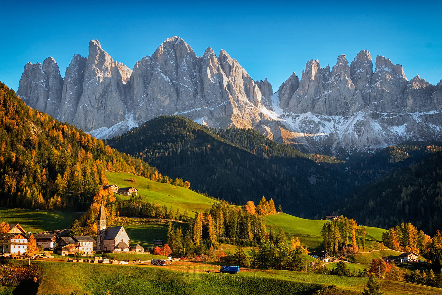 Landscape photo of St. Magdalena or Santa Maddalena village with its church in front of the Geisler Dolomites mountain peaks in the Val di Funes Valley (Villnoesstal) in South Tyrol, Italy in autumn.