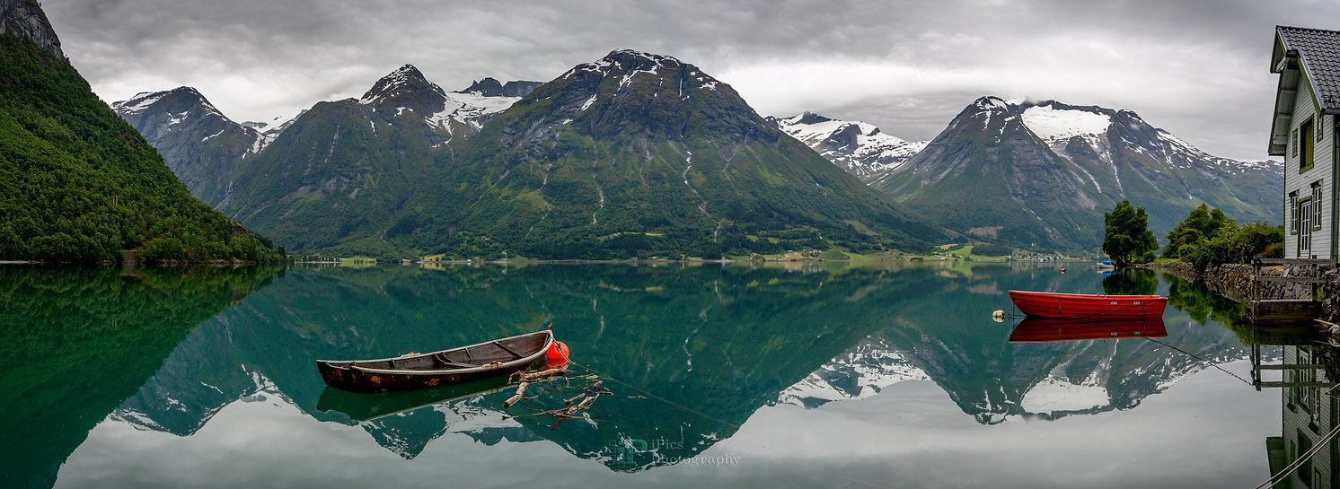 Photo of small boats in a still lake with mountains in the background in Norway.