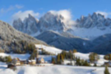 Landscape photo of St. Magdalena or Santa Maddalena with its characteristic church in the fresh snow in front of the Geisler or Odle dolomites mountain peaks in the Val di Funes (Villnosstal) in Italy in winter.