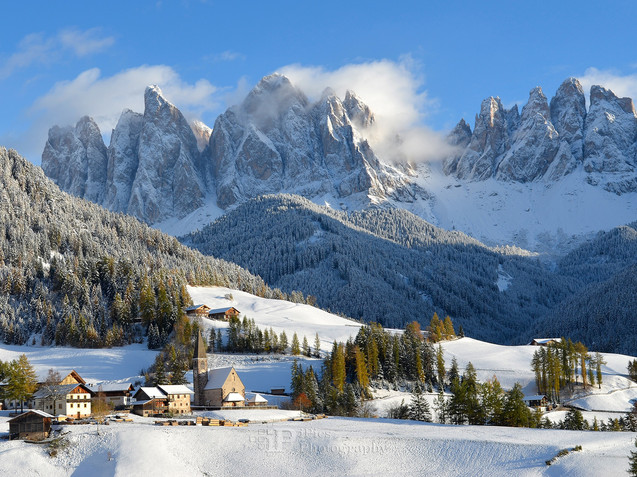 Sankt Magdalena in front of Dolomites mountains in winter