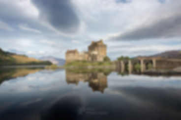 Postcard perfect photography of historic Eilean Donan castle bathing in the early morning light with great clouds in the sky and with reflection in the still water of the lake surrounded by mountains in a typical Scottish Highlands landscape near Skye, Scotland, UK.