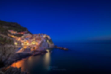 Night photo of the colorful town of Manarola, with lights on, built upon a cliff above the Mediterranean Sea and one of the five cinque terre villages near La Spezia, Liguria, Italy during blue hour.