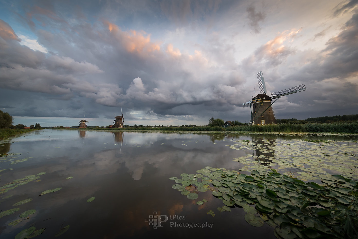 Big rain clouds creating a dramatic sky over a landscape with three windmills at the side of the river with reflection in the water during a summer storm in Leidschendam, the Netherlands.