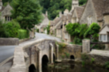 Photo of the quaint fairy tale village of Castle Combe at the border between the Cotswolds and Wiltshire with its characteristic bridge.