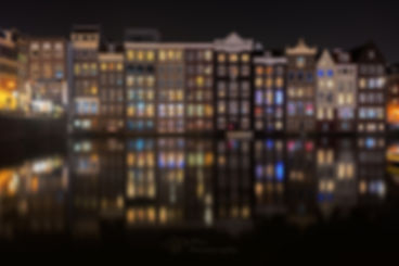 Colorful lights shining through the windows of the traditional canal houses and reflecting in the water at the Damrak at night in Amsterdam, the Netherlands.
