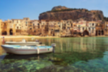 Travel photo of two dinghy boats in the transparent emerald green water of the small port at the city beach in the old town of Cefalu near Palermo in Sicily with crooked houses in typical waterfront architecture.