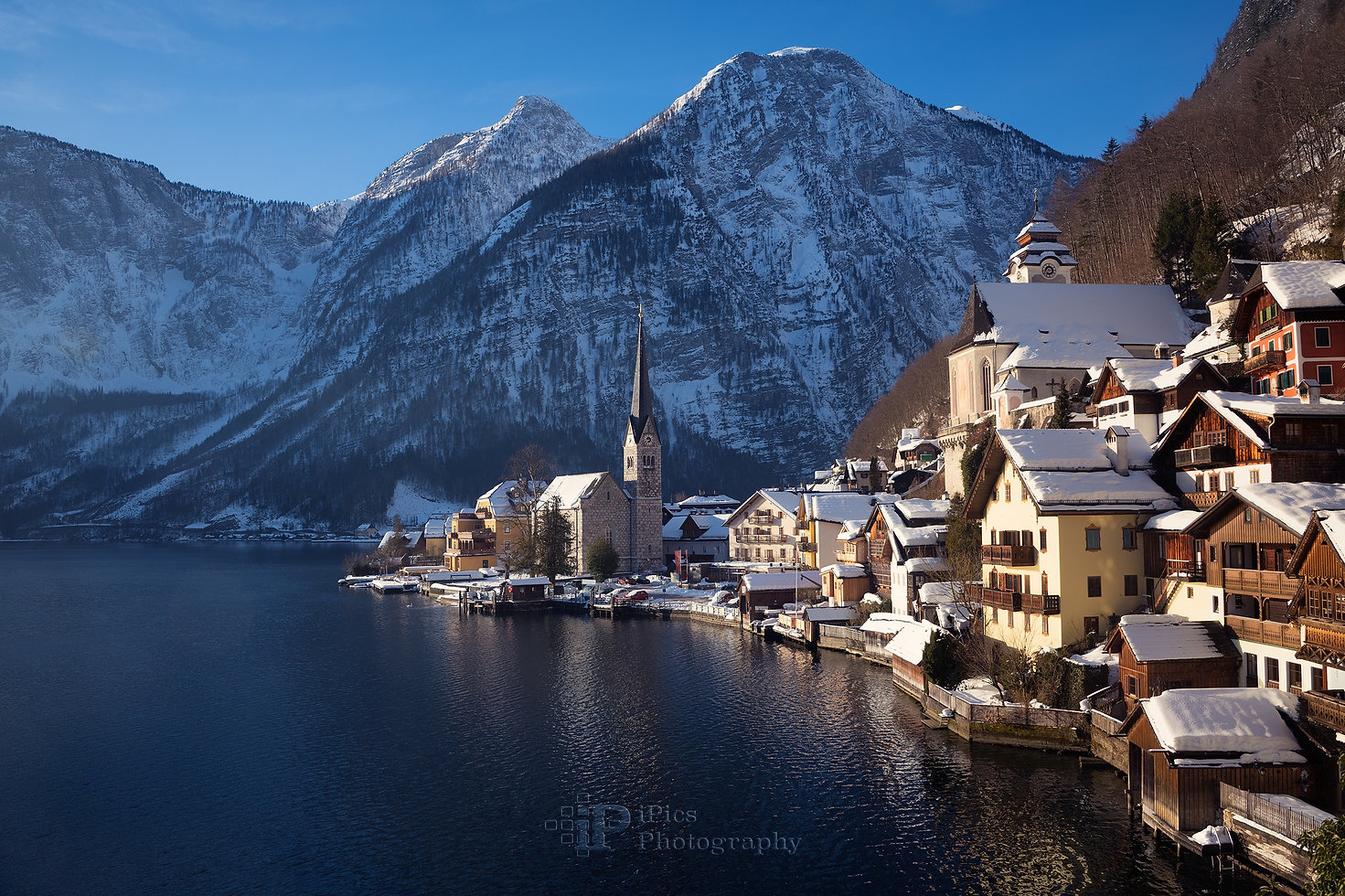 Landscape photograph of the church and houses in the village of Hallstatt with snow on the roofs at the shore of Hallstaetter See lake and surrounded by Alps mountains at sunrise on a beautiful blue sky winter day in Gmunden, Upper Austria.