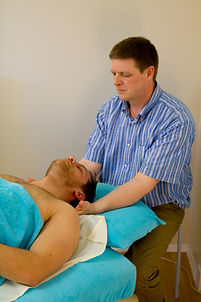 Stephen Hunter massaging the neck of a patient.