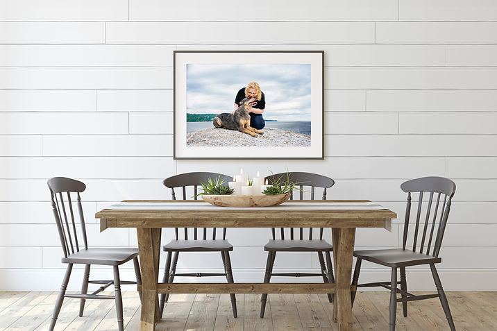 a large framed picture of a dog being kissed by his owner sits in a dining room