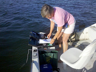 CHNEP Volunteer collecting seagrass data on a boat.