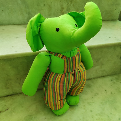 Green standing soft toy elephant with trunk up wearing stripped dungarees