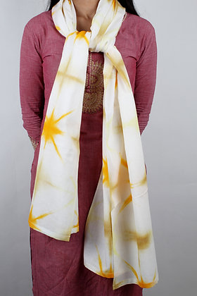White handwoven cotton scarf with marigold coloured resist dyed pattern