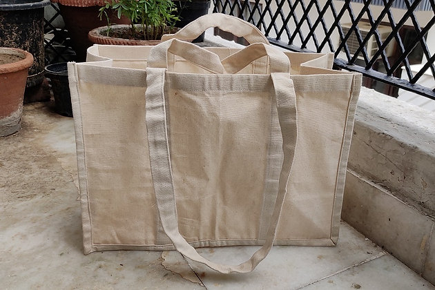 Large canvas bag with long and short handles standing on the ground