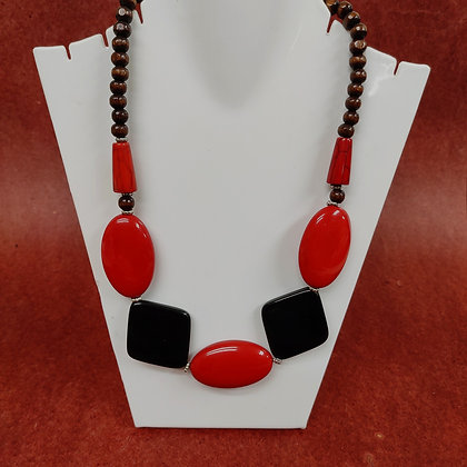 Necklace made of shiny bright red oval and also black diamond shaped resin beads and small wooden beads.