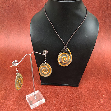 Pendant and earring set.  The pendant and earrings are made of clear resin with a brown spiral decoration.