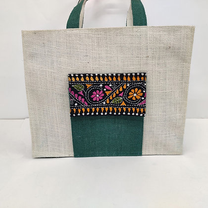Jute bag with an embroidered pocket and zip closure. The bag is natural and the pocket and gusset are green