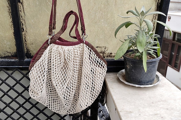 Natural coloured string bag with a set of short handles and longer handles attached with a metal clip