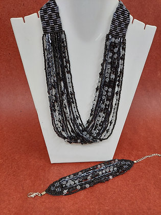Black & clear glass bead multi strand  necklace and bracelet set. The bracelet closes with a white metal chain and lobster c
