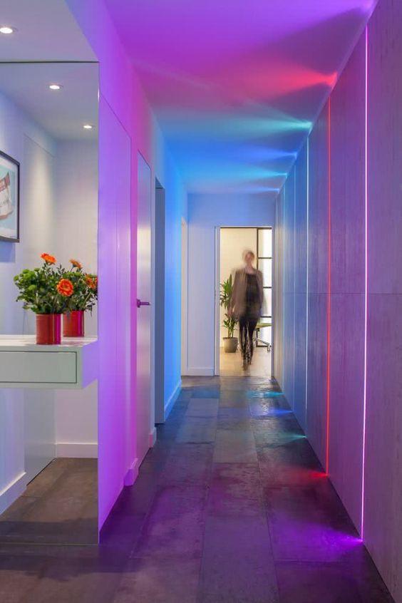 Corredor com filetes de LED colorido na parede.