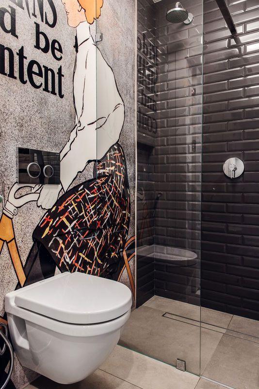 Banheiro estilo industrial com papel de parede desenhado.