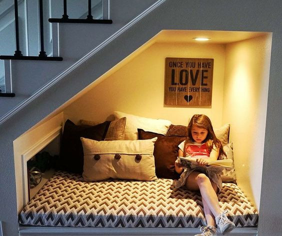 Espaço para leitura abaixo da escada com iluminação artificial.
