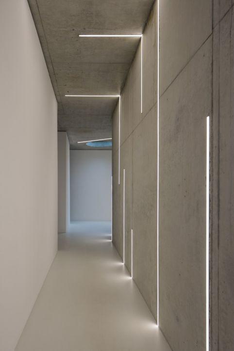 Corredor com filetes de LED branco na parede.