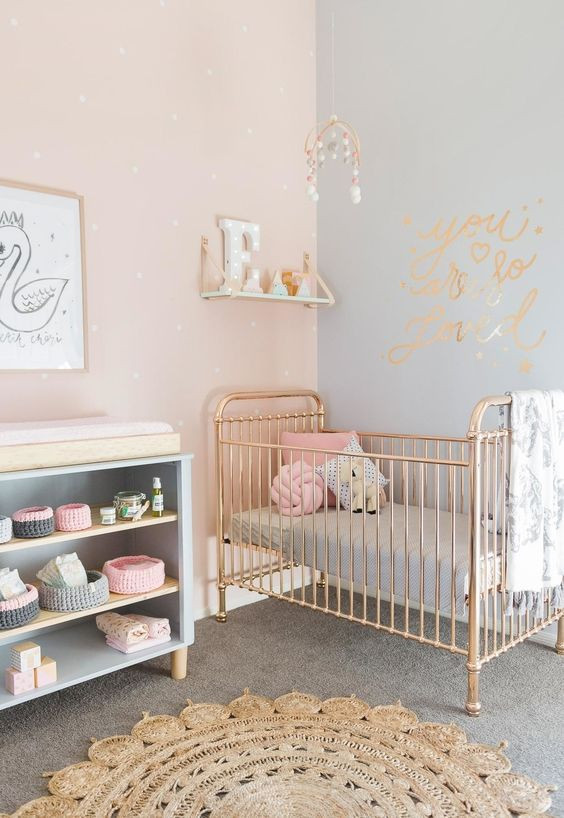 Quarto de bebê rosa, cinza e dourado.