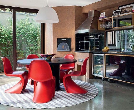 Área gourmet com cadeiras vermelhas.