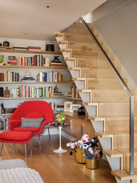 Estante de livros abaixo da escada.