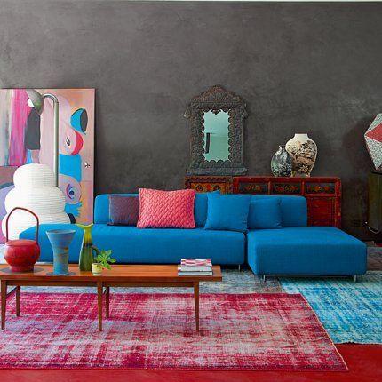 Sala com sofá azul e adornos coloridos.