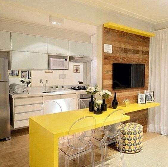 Salas integradas com balcão amarelo.