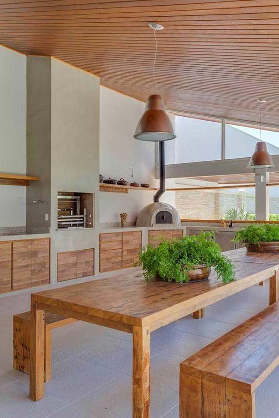Área gourmet com churrasqueira e forno de pizza.