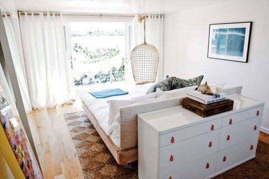 Quarto de casal com cama em ilha de frente para a janela.