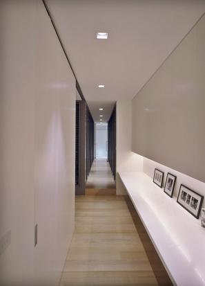 Corredor com nicho iluminado na parede.
