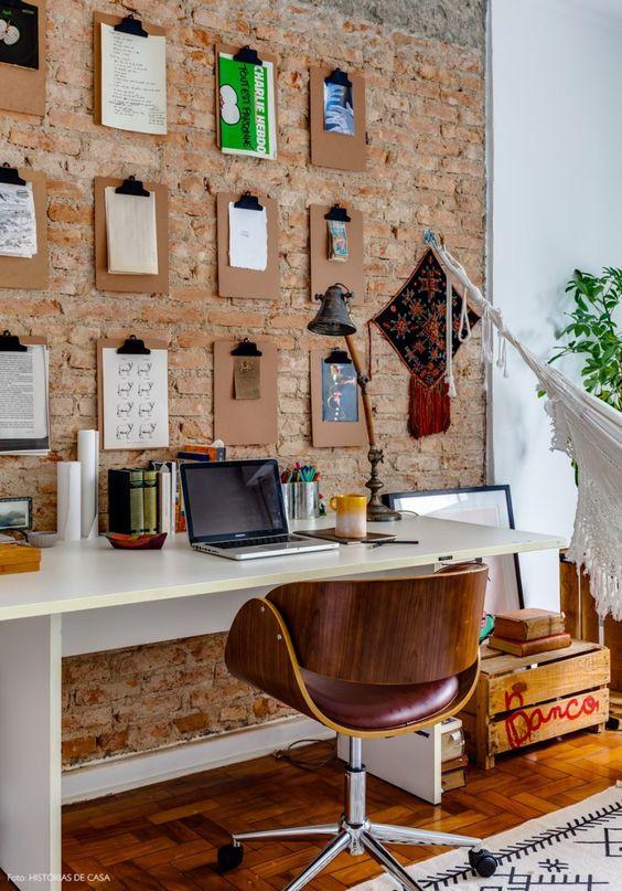Escritório com pranchetas na parede de tijolinho. Foto: Histórias de casa.
