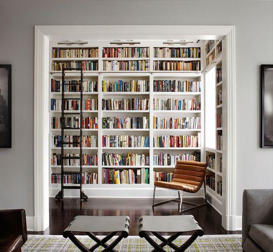 Estantes de livro alta com escada.