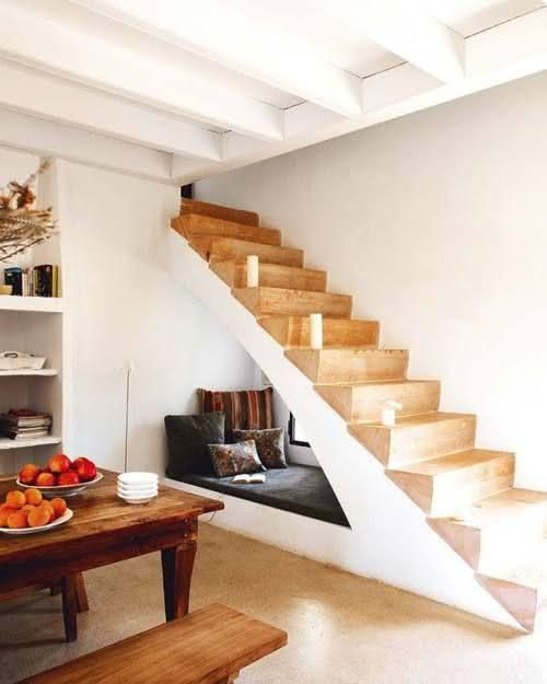 Espaço para leitura abaixo da escada com iluminação natural.