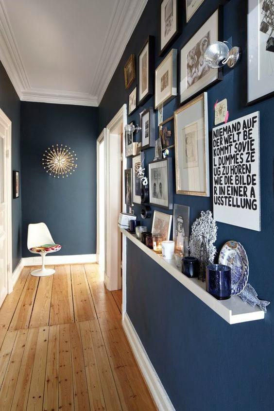 Corredor com prateleira e quadros na parede.