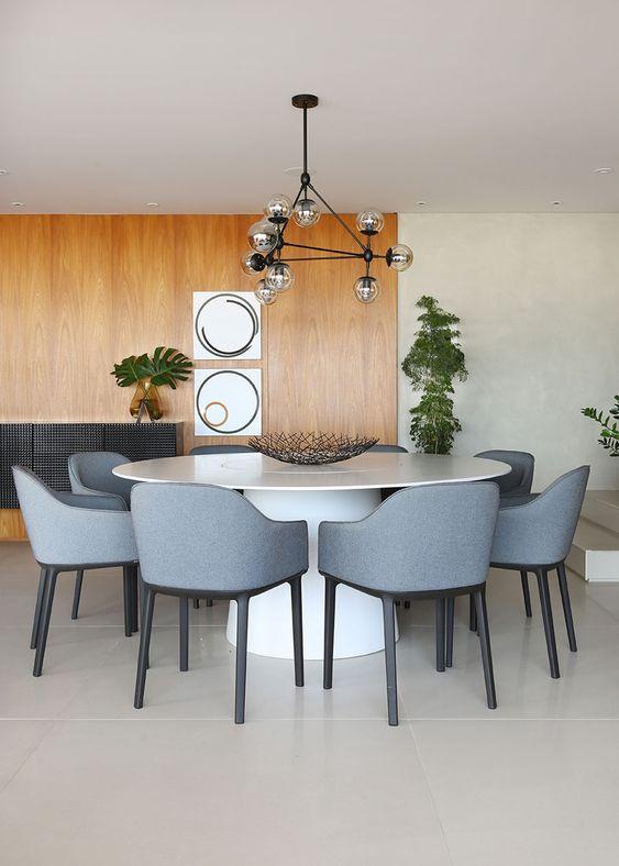 Sala de jantar com mesa redonda e cadeiras fluidas. Loft87 Arquitetura.