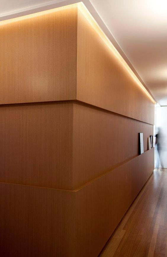 Corredor com painel em madeira. Projeto: Paula Magnani.