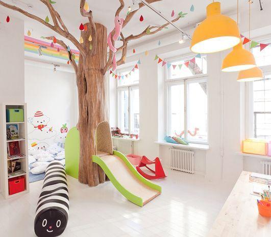 Brinquedoteca com árvore e escorregador.
