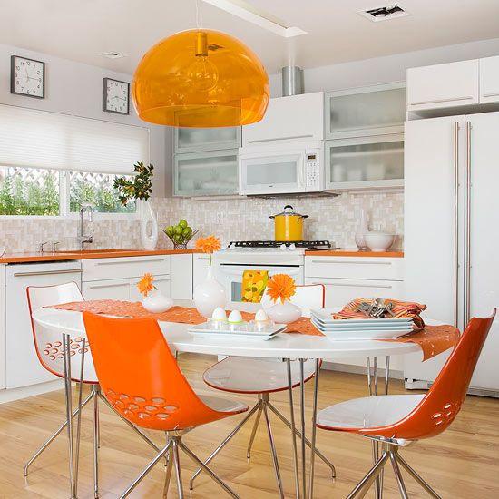 Cozinha com cadeiras e bancada laranja.