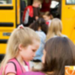 Blondes Mädchen mit seiner Mutter am Morgen vor dem Einstieg in den Schulbus, zeigt Trennungsängste.