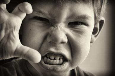 Kleiner Junge macht eine drohende Geste und zeigt aggressives Verhalten.