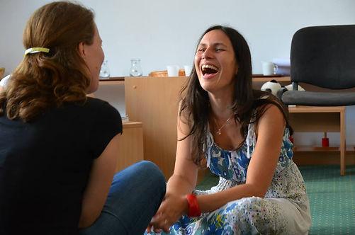 Zwei Mütter sitzen sich gegenüber und Lachen während sie sich Zeit für ihre Listening Partnership nehmen.