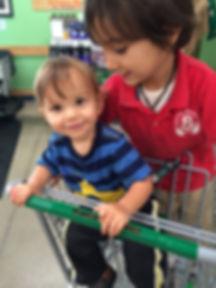 Zwei kleine Jungs - Geschwister - beim Einkaufen im Supermarkt. Der Kleinere sitzt im Einkaufswagen. Sie verstehen sich im Moment gut.