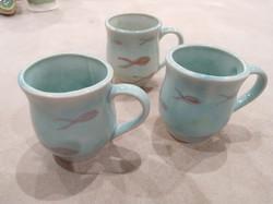 Three slip cast mugs with underglaze col