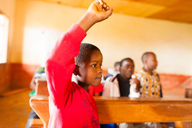 Cameroonian child raising hand in class at school