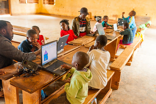Cameroonian children using laptops to create pictures.
